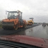 Омичи застали дорожников за работой в дождь