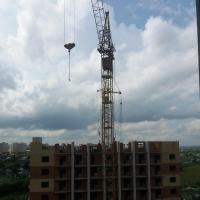 В Омске кран угрожающе навис над балконами жилого дома