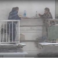 Омичи установили столик между балконами на третьем этаже и выпивают