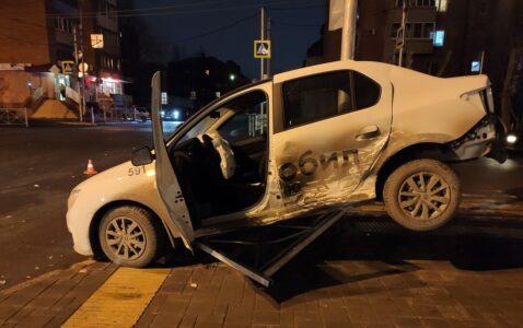 Автомобиль «такси» повис на заборе в центре Омска